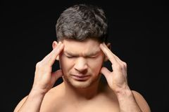 Handsome young man suffering from headache. On dark background Stock Image