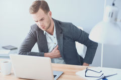 Handsome young man suffering from heartache by the working place. Filling bad. Good looking young man suffering from heartache and working on laptop while Stock Photo