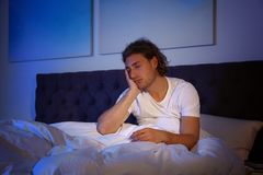 Handsome young man suffering from insomnia in dark room royalty free stock photos