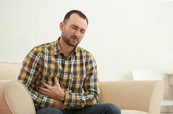 Handsome young man suffering from stomach ache. At home Royalty Free Stock Photo