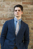 Handsome young man in suit against brick wall Royalty Free Stock Photo