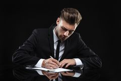 Handsome young man in suit on dark background Royalty Free Stock Images
