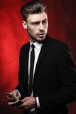 Handsome young man in suit on dark background with Royalty Free Stock Images