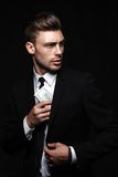 Handsome young man in suit on dark background with royalty free stock photo