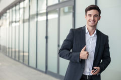 Handsome young man in suit is gesturing positively Stock Photo