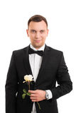 Handsome young man in a suit holding a flower Stock Photo