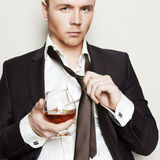 Handsome young man in suit toasting cognac Royalty Free Stock Photography
