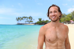 Handsome young man on summer beach vacation. Handsome young man smiling looking at turquoise ocean on summer beach vacation. Portrait of an attractive caucasian royalty free stock images