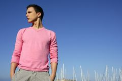 Handsome young man on summer in harbor. Blue sky Royalty Free Stock Photo