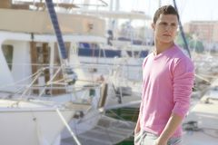 Handsome young man on summer in harbor. Boats background Stock Photos