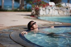 Handsome young man in sunglasses lays in swimming pool resting. happiness, summer travel vacations hotel. Royalty Free Stock Photo