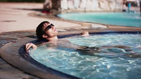 Handsome young man in sunglasses lays in swimming pool resting. happiness, summer travel vacations hotel. 1920x1080. Handsome man in sunglasses lays in swimming stock video