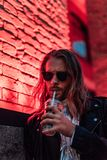 handsome young man in sunglasses and leather jacket drinking take away cocktail from plastic cup under red light stock images