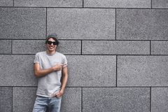 Handsome young man with sunglasses is pointing away, looking at camera and smiling, standing against gray wall. stock images