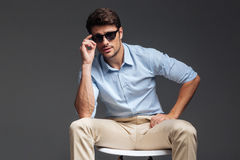 Handsome young man in sunglasses sitting on the chair royalty free stock photography