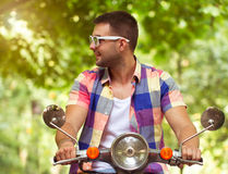 Handsome young man in sunglasses sitting on a scooter Stock Image
