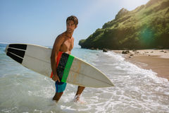 Handsome young man with surfboard on the beach Stock Images