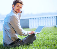 Handsome young man surfing  internet pages outdoor Royalty Free Stock Photo
