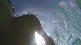 Handsome young man swimming in pool, underwater shot stock video footage