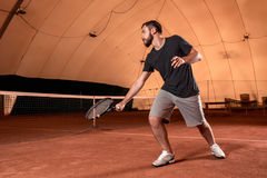 Handsome young man in t-shirt holding tennis racket on tennis court Royalty Free Stock Photos