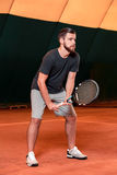 Handsome young man in t-shirt holding tennis racket on tennis court Royalty Free Stock Images