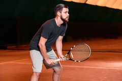 Handsome young man in t-shirt holding tennis racket on tennis court Stock Photography