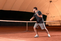 Handsome young man in t-shirt holding tennis racket on tennis court Royalty Free Stock Photography