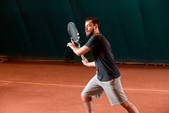 Handsome young man in t-shirt holding tennis racket on tennis court Stock Images