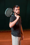 Handsome young man in t-shirt with racket on tennis court Royalty Free Stock Photography