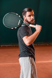 Handsome young man in t-shirt with racket on tennis court Royalty Free Stock Photos