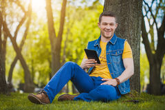 Handsome young man with tablet in the park Stock Images