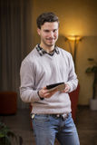 Handsome young man with tablet PC at home Stock Photo