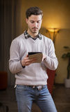 Handsome young man with tablet PC at home Royalty Free Stock Image