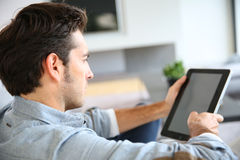 Handsome young man with tablet on sofa Royalty Free Stock Photos