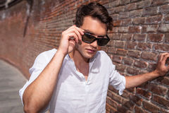 Handsome young man taking off his sunglasses. Stock Photo