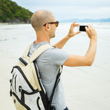 Handsome young  man taking photo with cell phone Stock Photos