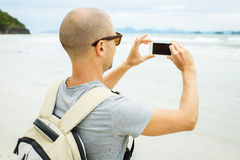 Handsome young  man taking photo with cell phone Royalty Free Stock Image