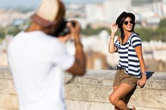 Handsome young man taking photo of his girlfriend in the street. Royalty Free Stock Photography