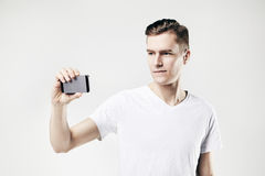 Handsome young man taking picture by mobile phone, isolated on white background, wearing white t-shirt. Stock Photo
