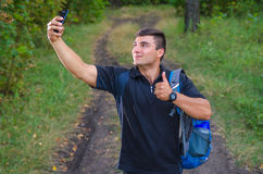 Handsome young man taking a selfie with a phone, smiling. graded with a flare, in instagram style. Handsome young man taking a selfie with a phone, smiling stock images