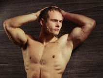 Handsome young man taking a shower. Male perfection. Closeup image of sexual gay man posing with his hands behind his head and looking away while standing under Royalty Free Stock Image