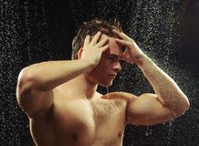 Handsome young man taking a shower. Sensual gay handsome. Closeup side view portrait of young sexy man exposing his body through the water drops while taking a Stock Images