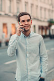 Handsome young man talking on cellphone in the city Stock Photos