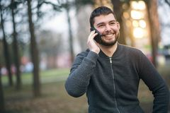 Handsome young man talking on his phone in an urban area Stock Photos