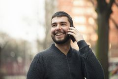 Handsome young man talking on his phone in an urban area Stock Photo