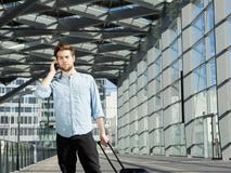 Handsome young man talking on mobile phone at airport with bags Stock Photo