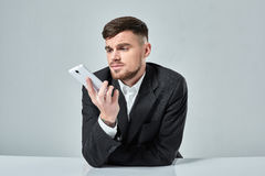 Handsome young man talking on the mobile phone while sitting at his working place in office Stock Photos