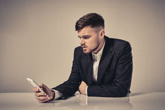 Handsome young man talking on the mobile phone while sitting at his working place in office Stock Image