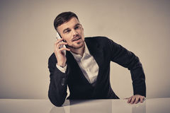 Handsome young man talking on the mobile phone while sitting at his working place in office Royalty Free Stock Images