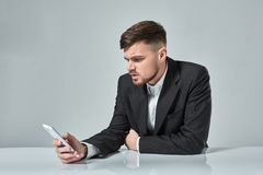 Handsome young man talking on the mobile phone while sitting at his working place in office Royalty Free Stock Photo
